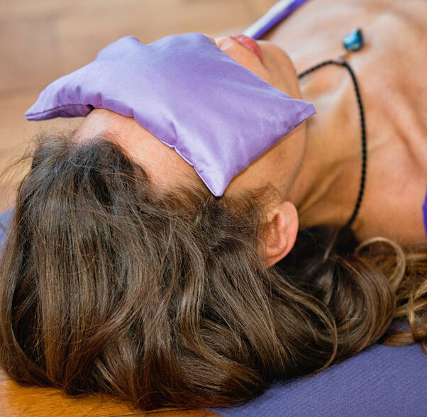 Woman in Yoga Savasana position with lavender eye pillow